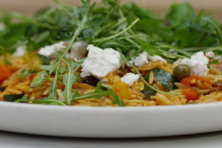 Deze lauwe pastasalade lepelt met gemak naar binnen. Die typische Griekse pasta in de vorm van grote rijstkorrels maakt er meteen iets bijzonders van.Verwacht je ook niet aan een smaakervaring vergelijkbaar met de vlammende uitlaat van de Space Shuttle, want de harissa die Jeroen maakt is gemaakt op basis van die gewone milde paprika