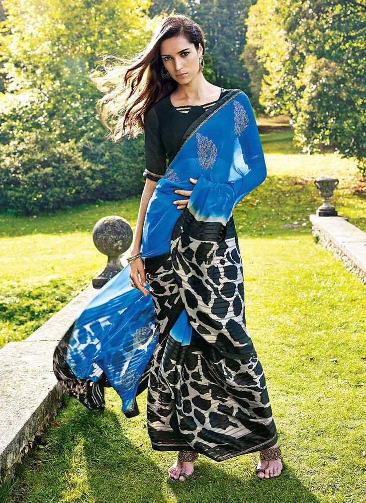 Blue And Black Color Georgette And Satin Saree Blue and black color georgette and satin fabric saree is crafted with abstract prints, self coloured satin stripes and stick on crystal enhanced foliage motifs highlight the first and second halves of the apparel. Comes with matching blouse.(Slight color variation is possible.)