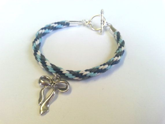 A handmade toggle bracelet made with a kumihimo brad of Winter themed colours (navy blue, light blue, grey and white) with a choice of charm.