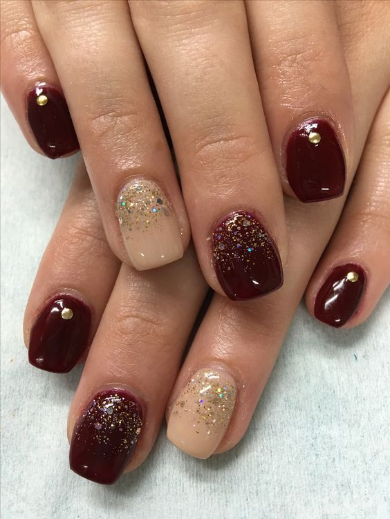 Burgundy, Nude, Gold Glitter ombre gradient and studs on hand sculpted gel nails. Are you looking for nail colors design for winter? See our collection full of cute winter nail colors design ideas and get inspired!