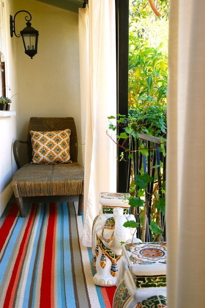 a Balinese-influenced chair, a pair of Asian elephants, a cheerful rug that calls to mind a serape, with a tangle of foliage curling in to give the setting a lushly verdant feel. this al fresco haven could be reinvented as a Mexican or Central American retreat. Imagine it with a colorfully painted, chunky wooden chair, handmade terra-cotta pots and a scrolled wrought iron railing entwined with bougainvillea.