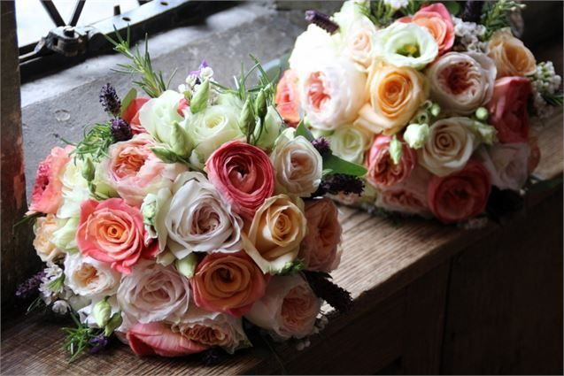 bridesmaids bouquets of ivory, blush, peach and coral roses, spray roses, lisianthus, wax flowers and lavender.  Wild wedding flowers bouquets.