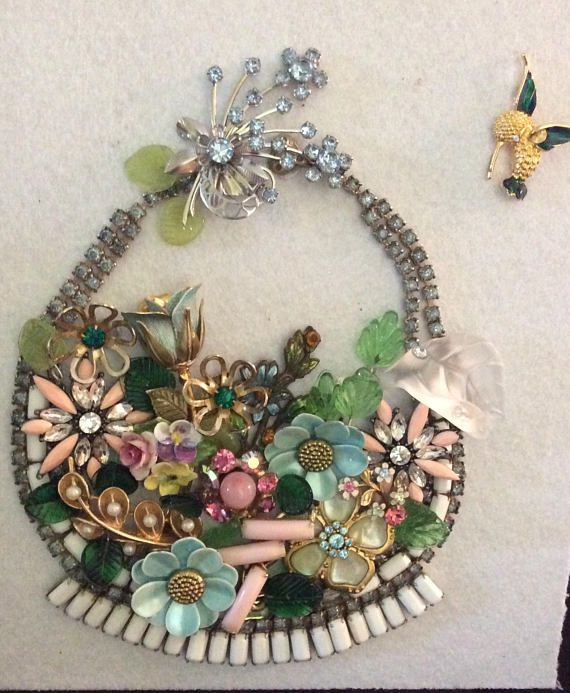 Pastel vintage floral themed jewelry in the shape of a basket filled with flowers. There is so much to tell about this piece. There is a large Swarovski Crystal leaf on the far right of the basket, Vintage glass leaves in different shades of green, enameled floral earrings and