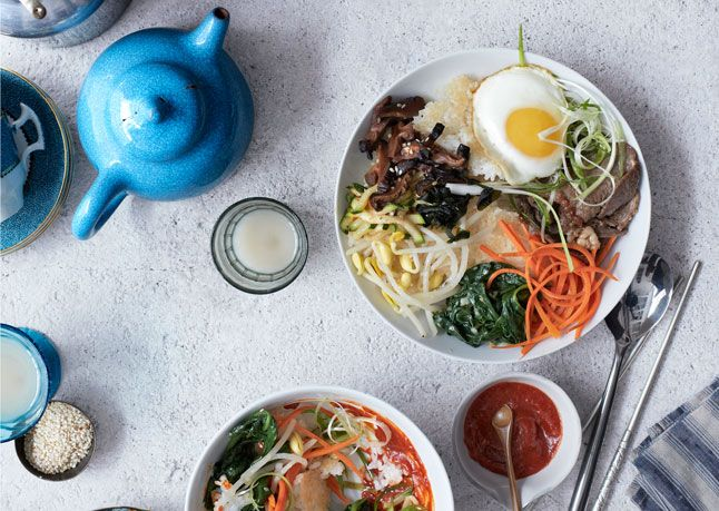 Bibimbap at Home. A Korean dish with crispy rice, sesame bean sprouts, carrots, garlicky spinach, soy-glazed mushrooms, fried egg, zucchini, scallions, and peanuts.