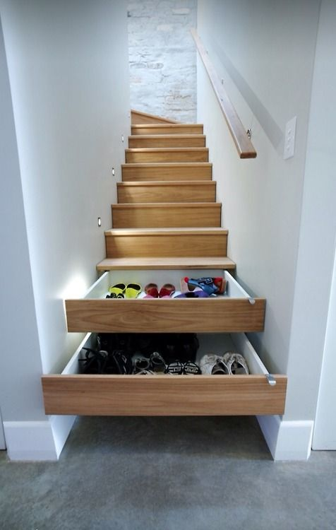Pull-out drawers for shoes, hidden in the staircase.