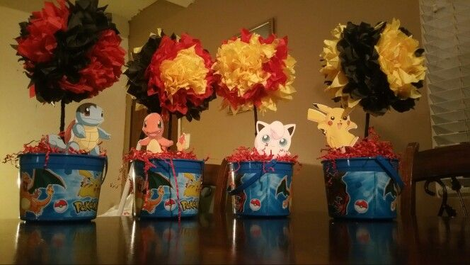 Really simple Pokémon centerpieces. I bought the buckets at party city and filled it up with grass paper made the tissue pompoms and printed the pokemon characters on cardstock paper. Really easy to make!!!! Loved the outcome