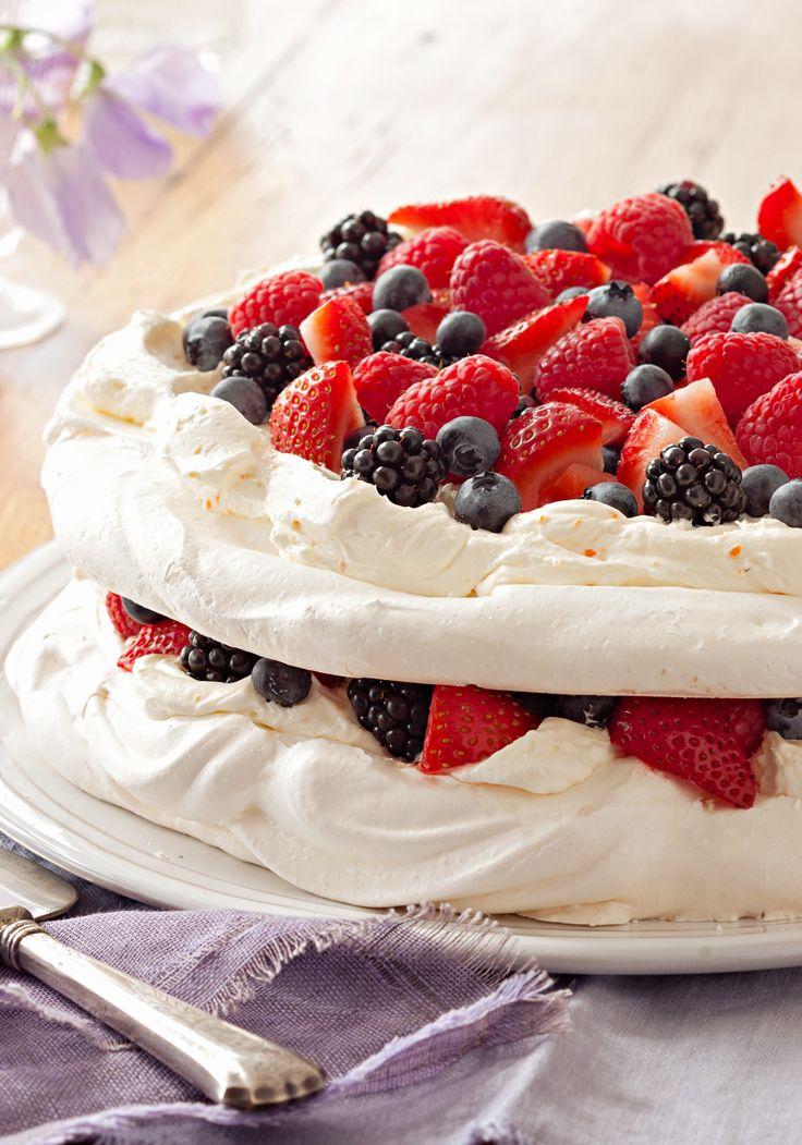 Pavlova en capas con bayas- Bayas de queso crema dulce y mezclado con moras- incluyendo fresas, moras azules, y frambuesas- están puestas por capas con merengue en esta pavlova con bayas.