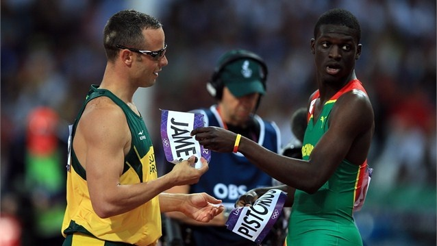 Oscar Pistorius of South Africa exchanges bibs with Kirani James of Grenada