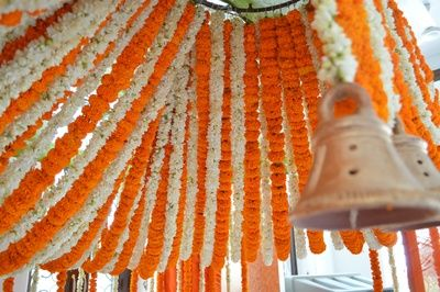 genda flower decor, ceiling decor, strings of white and orange, rustic temple bells, south Indian wedding decor