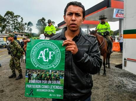 A fan of Colombia's football team Atletico Nacional holds a banner in memoriam of the Chapecoense footbal team members in La Union, Antioquia Department, Colombia on November 29, 2016. A charter plane carrying the Chapecoense Real football team crashed in the mountains in Colombia late Monday, killing as many as 75 people, officials said / AFP PHOTO / LUIS ACOSTALUIS ACOSTA/AFP/Getty Images