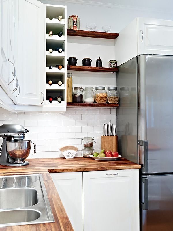 white cabinets, butcher block countertops, open wood shelving, stainless steel appliances, built in wine storage. pretty much my dream kitchen...