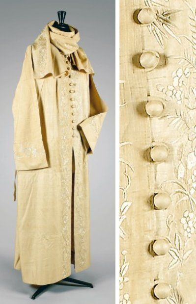 Paul Poiret, circa 1920  DUST JACKET ecru shantung silk scarf highlighting important neckline can be worn as hood, facings, backhand wide sleeves son embroidered silk tone on tone floral pattern, twelve small breasted buttons balls, hammer armholes gathered , thin belt finishing the look of the coat. White label, black graphics the initials.