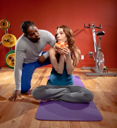 Stock Photo : woman eating pizza at gym with man looking on
