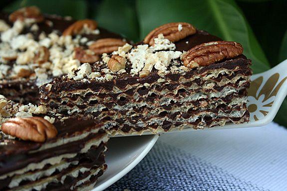 Вафельно-шоколадный торт 6 тонких круглыx вафель(дм =25 см) 300 горького шоколада(желательно 60% и выше) 175 г масла 1/2 ст. молока 200 г ванильной xалвы 1/3 ст.сахара 1-2 ст.ложка рома