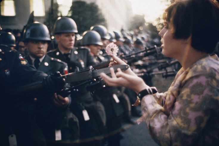 """""""La Jeune Fille a la Fleur,"""" a photograph by Marc Riboud, shows the young pacifist Jane Rose Kasmir planting a flower on the bayonets of guards at the Pentagon during a protest against the Vietnam War on October 21, 1967. The photograph would eventually become the symbol of the flower power movement."""