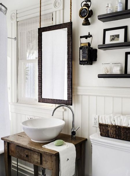 Reclaimed wood vanity with mirror on chains above white vessel sink. Room is panelled in wood painted white.  www.mulberryinteriors.ca