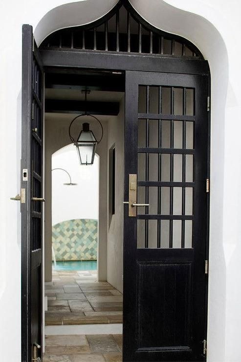 Mediterranean front door opens to a passage way to the pool.