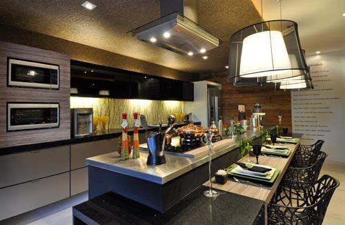 A cozinha gourmet é totalmente integrada aos outros ambientes, com apenas a bancada como limite de espaços.