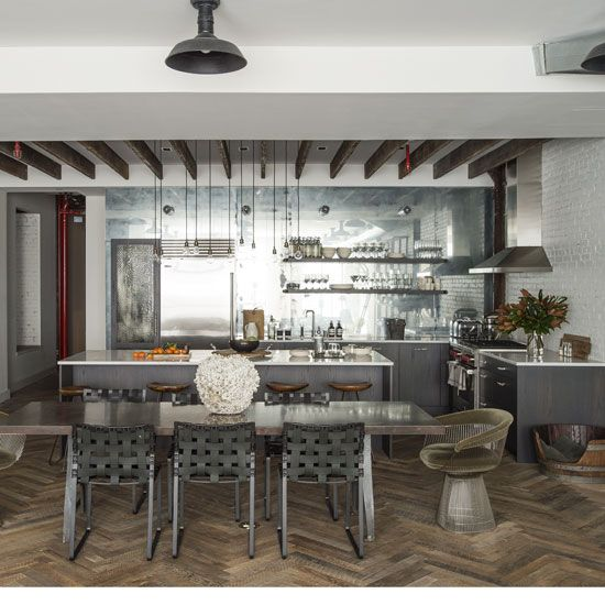 The back wall of this edgy, industrial-chic kitchen-diner is clad in antiqued mirror