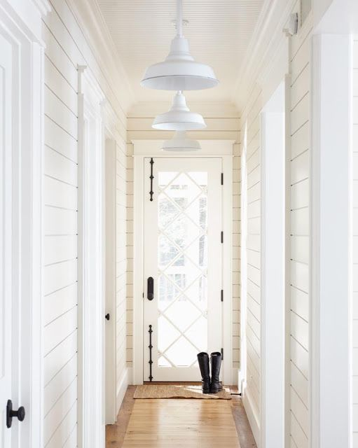 Make an Entrance. A custom door with dramatic dark hardware and white walls. Interior Design: Muskoka Living Interiors.