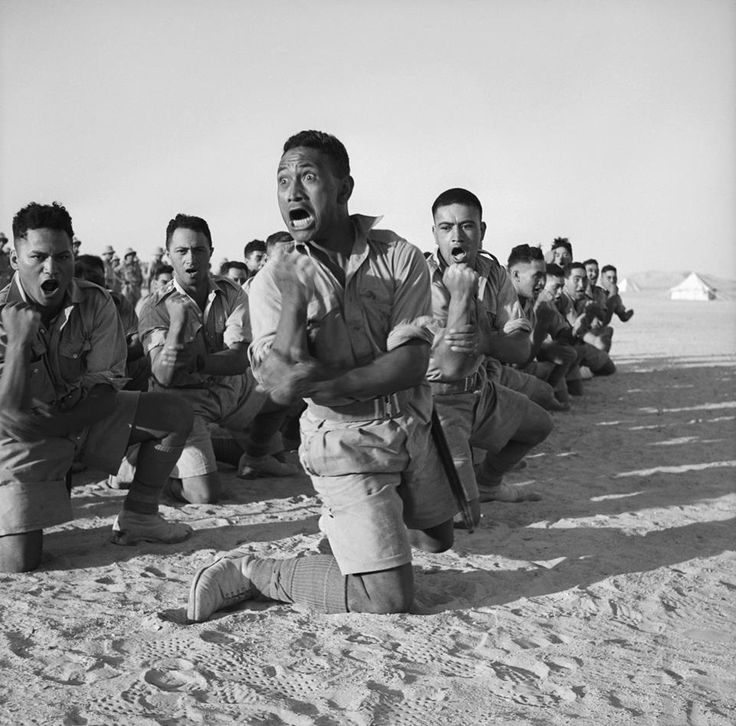 "Māori Battalion performing the Haka in Egypt, 1941. The four men in the foreground are, from left to right: John Manuel (later killed in action), Maaka ""Bill"" White (later killed in action), Te Kooti ""Scotty"" Reihana (later wounded), and Rangi Henderson (later killed in action)."