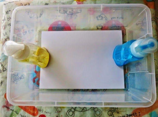 Una caja de plástico, 2 dispensadores de jabón en espuma y una hoja, hacen una actividad en casa muy divertida en la que puedes estimular el lenguaje, enseñarle al pequeño los colores primarios, mejore su fuerza y ¡que sea creativo!   Utiliza los dispensadores de jabón en espuma para darle a la pintura ese efecto. Mezcla dentro un poco de pintura espesa, jabón para lavar platos y un poco de agua.