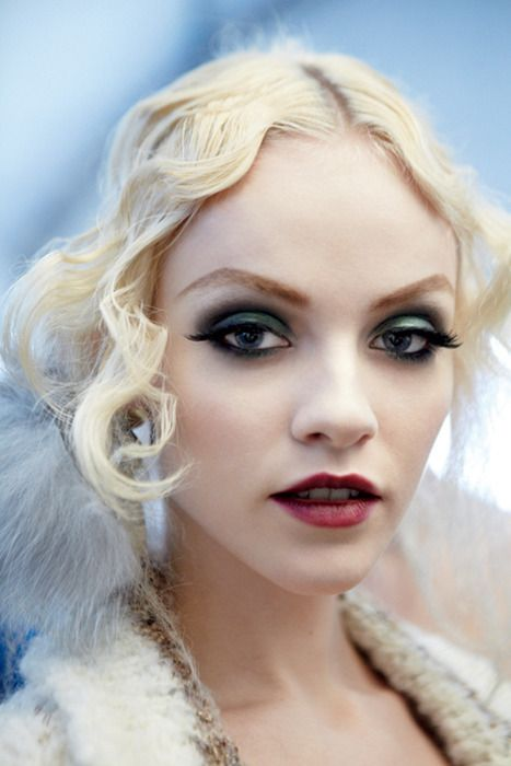 Modern Flapper Makeup:  Porcelain Face  Dark Smudgy Smokey Eyes Flippy Eyelashes Reshaped Red Mouth  Pronounced Eyebrows
