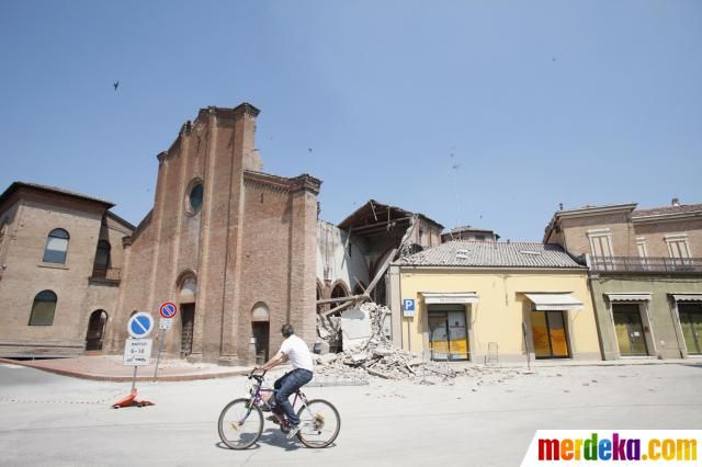 Seorang warga bersepeda melintasi bangunan yang rusak akibat gempa di Cavezzo, Modena, Italia, Selasa (29/5).