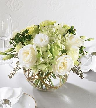 White and light green roses, gorgeous green hydrangea and green carnations along with white lisianthus accented with seeded eucalyptus and curly willow arranged in a clear glass bubble bowl. Your purc
