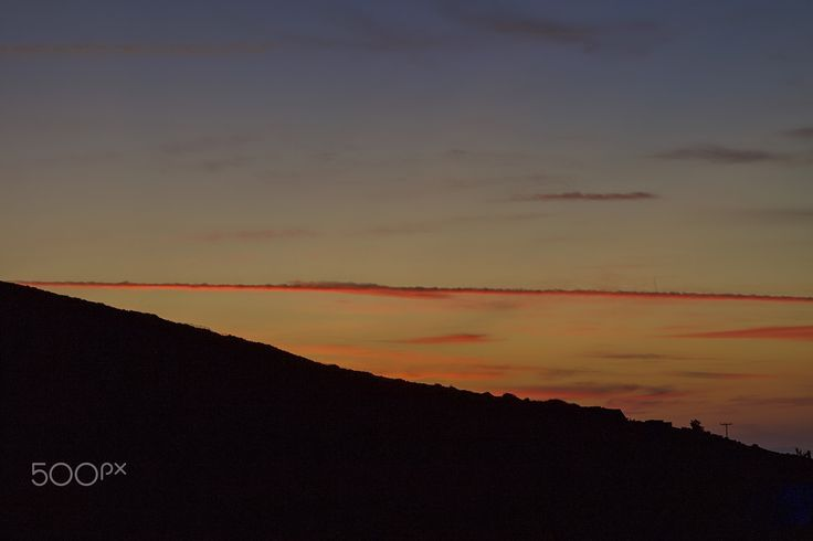 Different Sunset - Plane's trail in a  straight line  on the horizon being lit  by  the Autumn sunset.