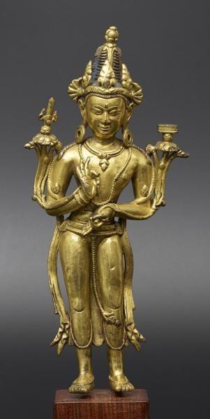 MANJUSHRI  TIBET CA 13°-14° SIÈCLE  Alliage cuivreux doré. H. 30 cm  Représenté debout en tribhanga le bodhisattva tient dans ses mains les tiges des lotus qui s'épanouissent au dessus de ses épaules, supportant les attributs, glaive et livre, qui permettent de l'identifier.  Il est richement paré et coiffé d'un haut chignon dans une combinaison stylistique mêlant des éléments empruntés aux modèles de l'Inde Pala aux apports des artistes Newars.