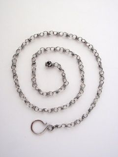 Karina's chains are entirely handmade from Sterling Silver wire.   Each link has been individually hand-wound and looped into the next, so the chains are continuous and strong - there are no open rings at all.   They feature a handforged clasp, and a little wire ball drop at the end, and can be clasped at any link along their length, making them quite versatile. To finish, Karina oxidises and polishes the silver so that they perfectly match her Antiqued Sterling Silver Handcrafted Pendants…