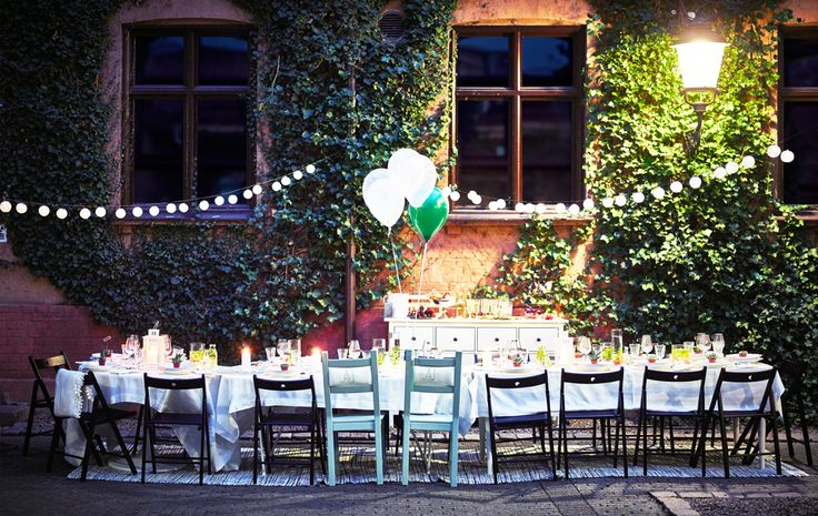 A dining table for a wedding is set up in a courtyard at night time.
