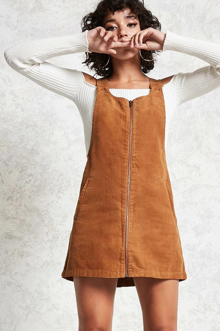 A corduroy overall dress with an exposed zippered front, slanted front pockets, and hidden buttoned straps.