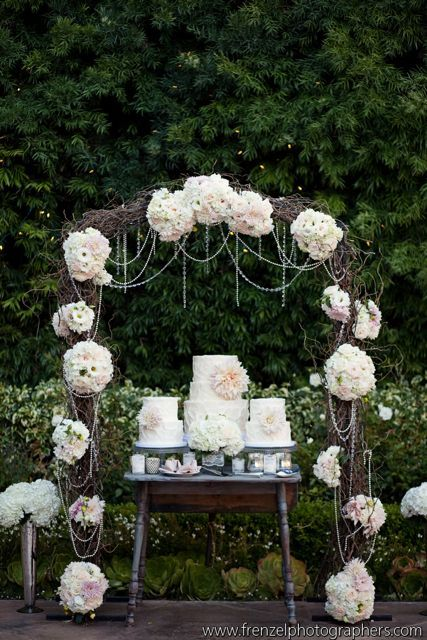 Twig arch with oversized flowrs and pears to display desserts...