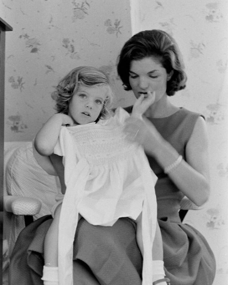 Jacqueline Kennedy gets her daughter, Caroline, dressed, 1960