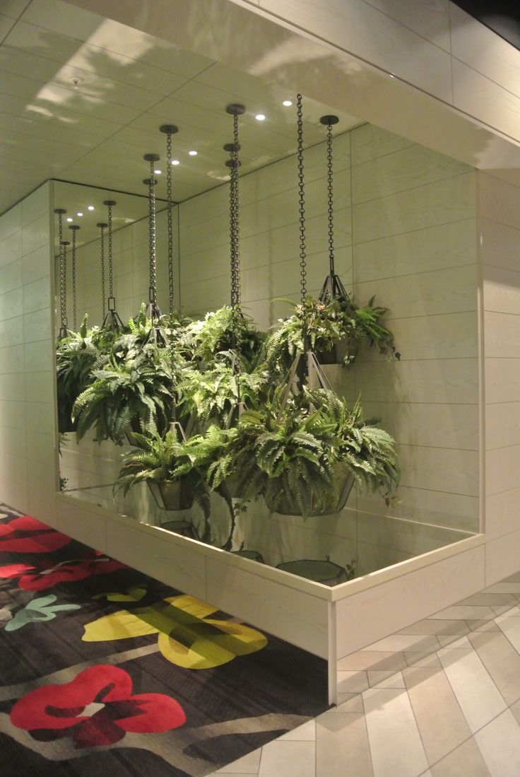 The corridor has been filled with a suspended garden. The mirros create an illusion of continuity which make the space look bigger