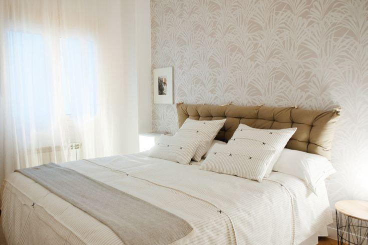 Papel pintado, cabecero de tela y funda nórdica a rayas blanco y negro, que combinan y hacen el dormitorio principal con estilo.