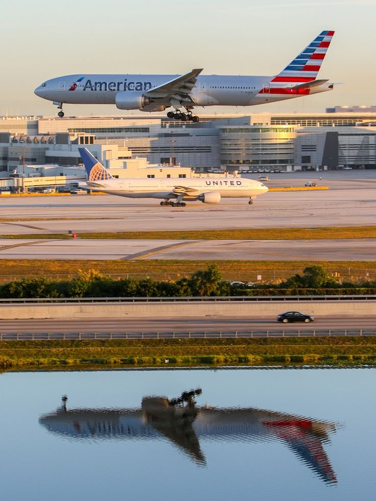 American Airlines Boeing 777-223/ER landing with its reflection visible in the water; a United Airlines 777-222/ER is seen taxiing on the apron