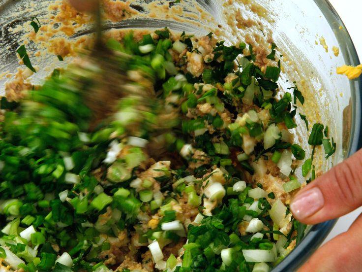 Сварить яйца вкрутую. Тем временем мелко нарезать лук и зелень.