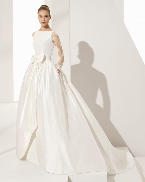 Elegance and classic styling combine in this silk taffeta dress with sleeves and beaded lace back. The silk taffeta overskirt attached to the bodice by the couture bow detail at the waist gives it spectacular yet lightweight volume and the option of two looks from a single gown — detaching the overskirt leaves an adorably […]