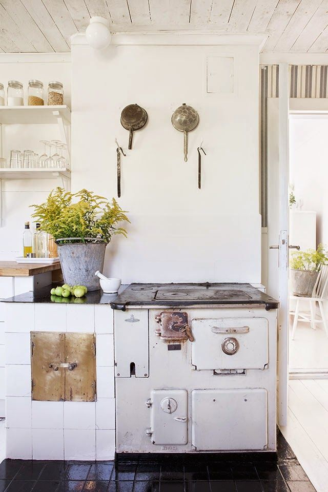 Rustic yet white kitchen with strainers hung above the stove as delightful accents.