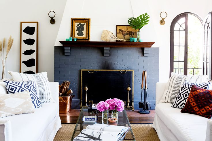 Brick fireplace painted blue in living room with white sofas, colorful pillows, leaning artwork, and pink flowers on glass coffee table: Brick fireplace painted blue in living room with white sofas, colorful pillows, leaning artwork, and pink flowers on glass coffee table