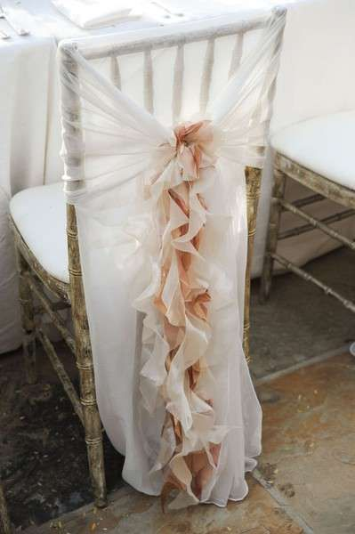 From A Low Country Wedding, this rustic wedding chair is dressed up with a sheer fabric and ruffles to match the white seat cover. Perfect!