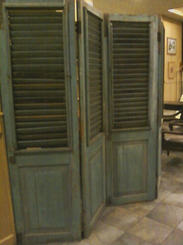 I saw this at a ritzy hotel.  Old door shutters were re-purposed into a room separator.
