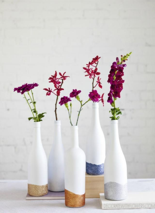 11 Ways to Upcycle Empty Wine Bottles: Glitter-Dipped Wine Bottle Vases. Turn your used wine bottles into centerpieces, vases, and more! Try these DIY projects with your friends.