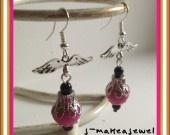 Boucles d'oreilles perles rondes roses ailées en fimo Perles roses 1,2cm de diamètre environ avec breloque argentées en forme aile de 2,5cm d'envergure.  La boucle d'oreilles fait environ 3,5cm de long en tout.