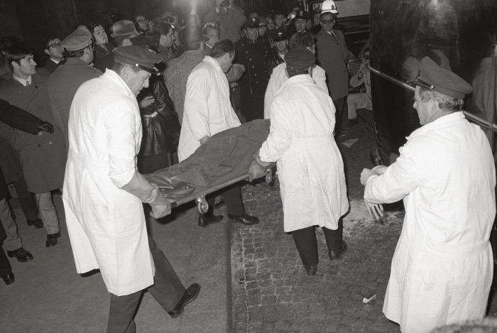 Agents take away one of the victims of the Piazza Fontana bombing. In the meanwhile, some curious people walking by crowd in to see, behind a police cordon. Milan, December 12th, 1969 MONDADORI PORTFOLIO/Sergio Del Grande