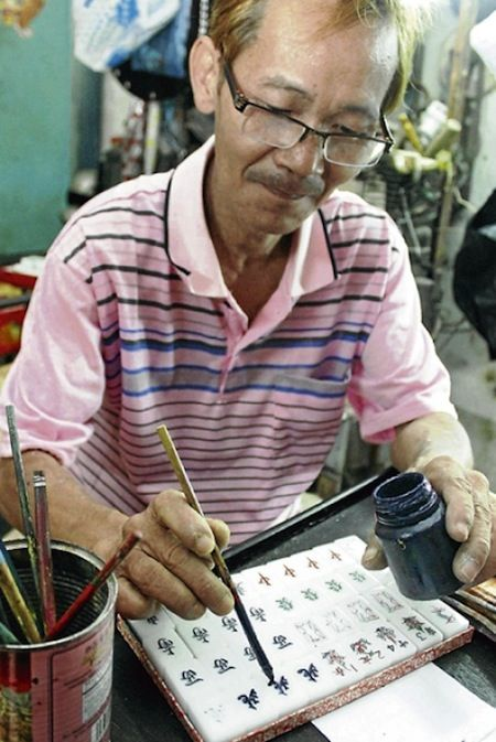 Ooi Hock Chye painting his handcrafted mahjong tiles.