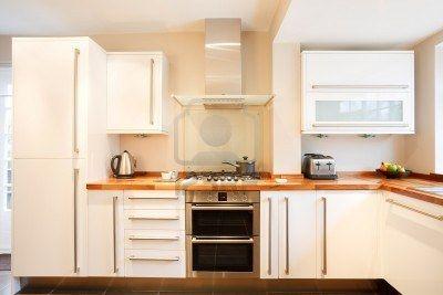 Cuisine blanc moderne avec des plans de travail en bois et en acier inoxydable appareils Banque d'images